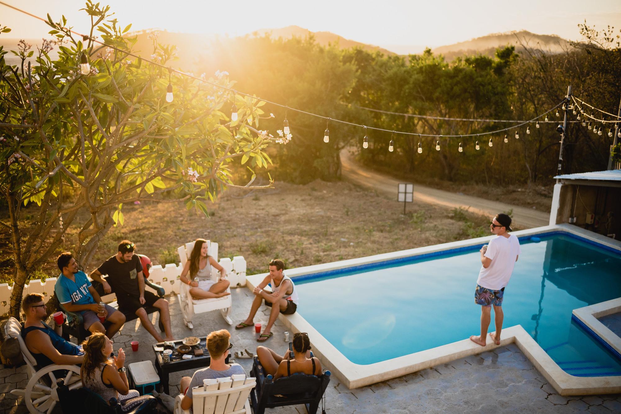 extérieur avec piscine et guirlandes lumineuses avec personnes assises qui boivent un verre