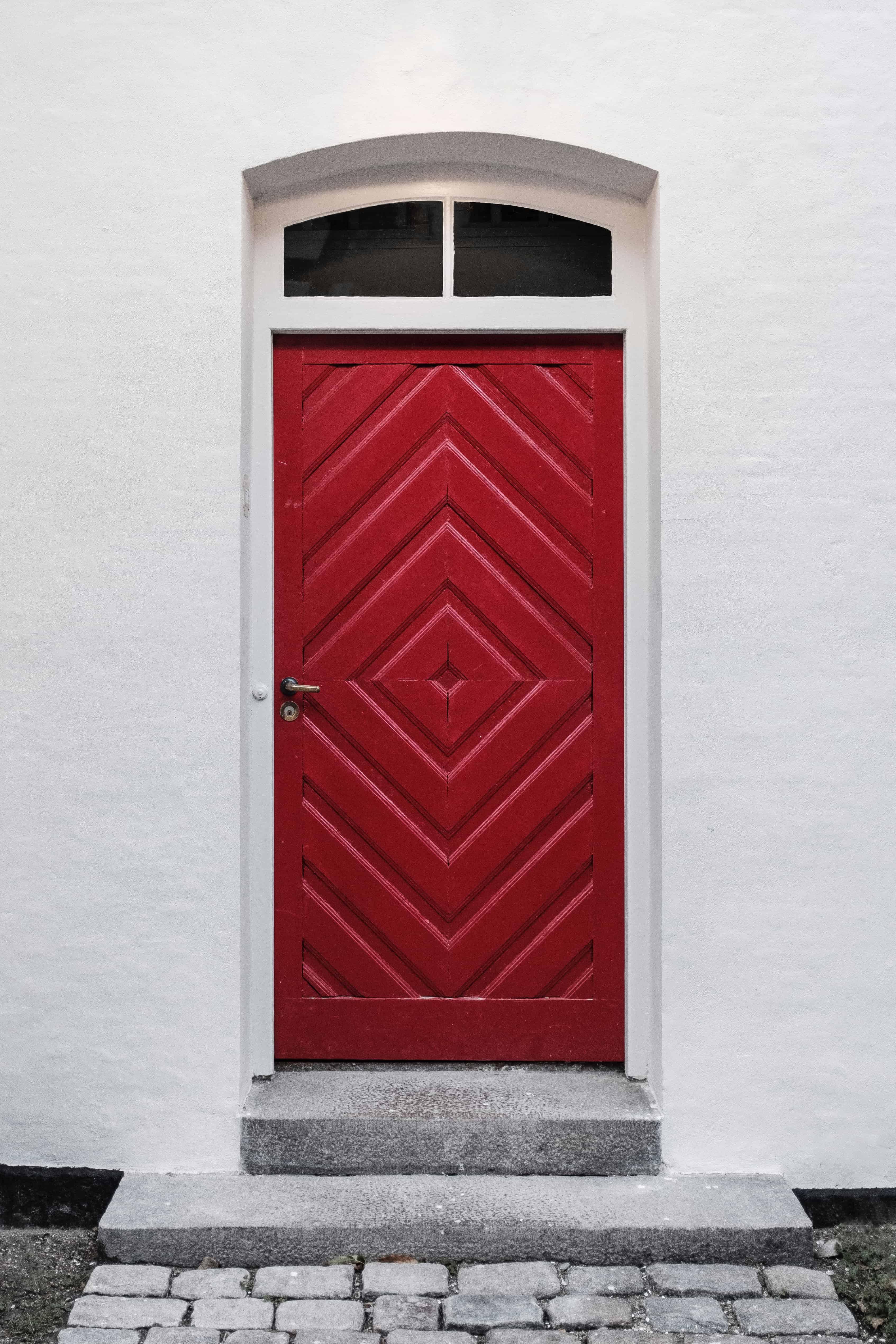 Une porte d'entrée rouge en bois avec motifs géométriques