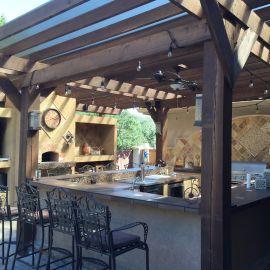 Une cuisine d'extérieur aménagée sous une pergola